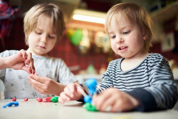 Два брата делают трехмерные фигурки из пластилина и палочек