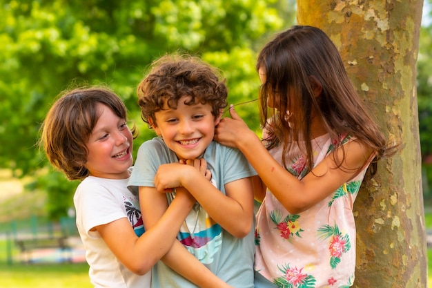 Two brothers and one sister smiling in a park next to a tree