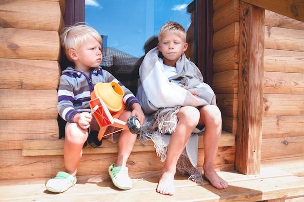 Два брата вместе играют на ступеньках своего дома.