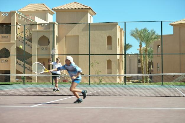 屋外のテニスコートで遊んでいる2人の兄弟