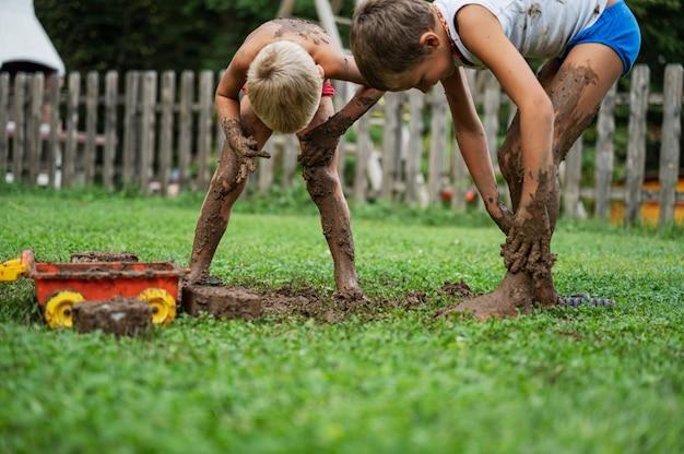 裏庭の外で泥で遊んでいる2人の兄弟が泥を自分たちのいたるところに広げています。