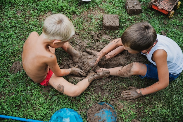 泥で遊ぶ2人の兄弟