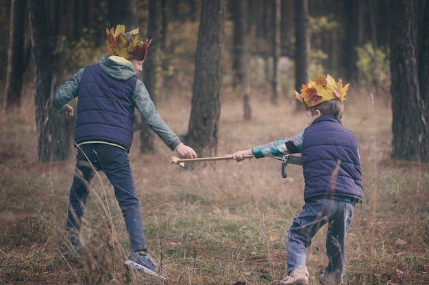 Two brothers running in a forest on autumn day.
