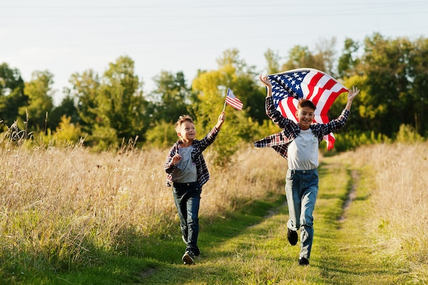 アメリカの国旗を掲げて走っている2人の兄弟。アメリカの休日。国の子供であることを誇りに思います。
