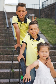 Two brothers and sister are standing on the stairs.