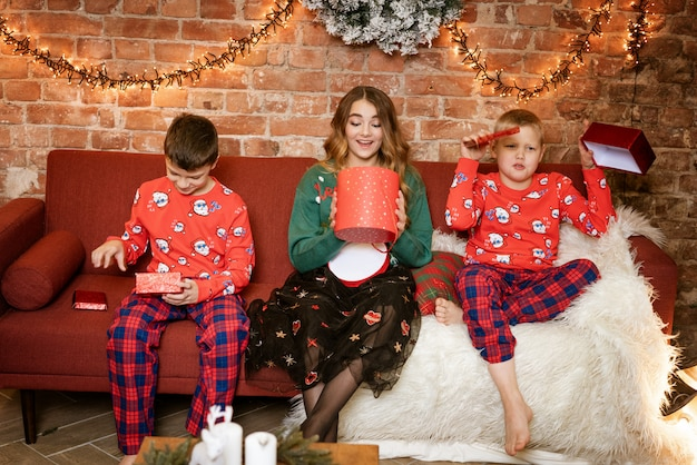 Two brothers and sister open gifts sitting on the sofa, happy faces, festive new year atmosphere