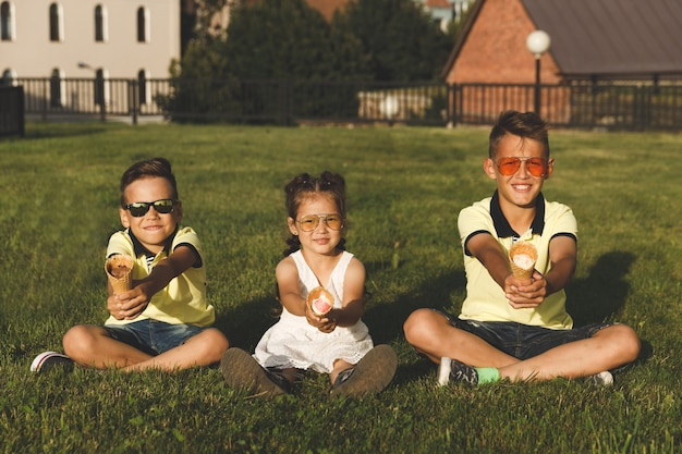 Two brothers and sister sit on the grass with ice cream.