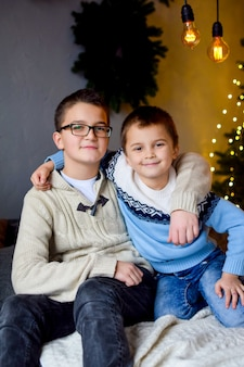 Two brothers sit on the bed and smile hugging each other in the decorated christmas living room