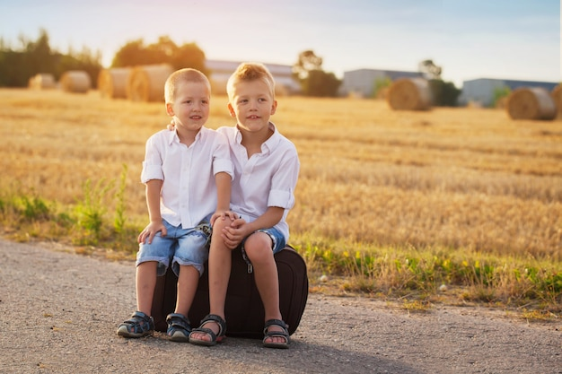 Two brothers sit on a suitcase on the road in the summer at sunset