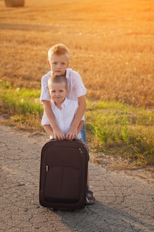 Two brothers with a suitcase on the road in the summer at sunset