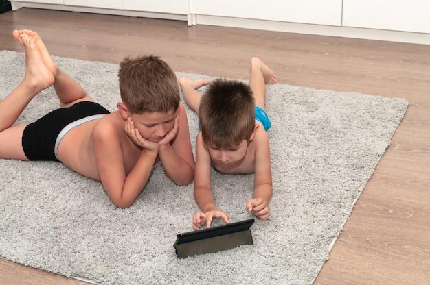 自宅の床に横たわっているタブレットコンピューターを持つ2人の兄弟。
