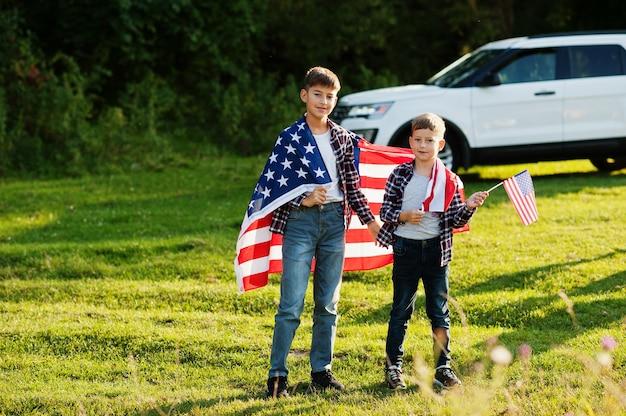アメリカの国旗を持つ2人の兄弟。アメリカの休日。国の子供であることを誇りに思います。