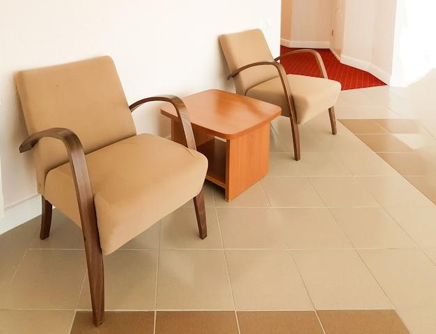 두 개의 갈색 안락의자와 그 사이에 있는 커피 테이블이 분홍색 벽, 현대적인 거실 또는 호텔 홀의 인테리어입니다.