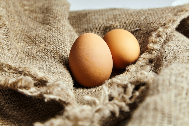 Two brown chicken eggs on sackcloth fiber