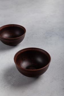 Две коричневые глиняные миски на светлом фоне