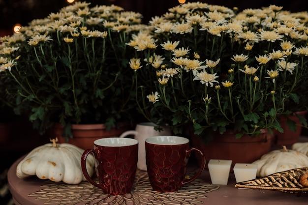 Две коричневые чашки на деревянном столе на фоне хризантем