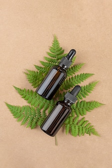 Two brown glass bottles with serum, essential oil or other cosmetic product and green fern leaves on craft beige background.
