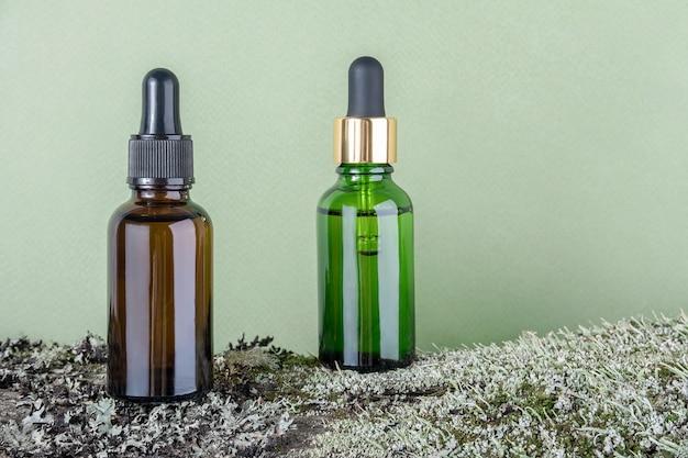 Две коричневые, зеленые стеклянные бутылки с сывороткой, эфирным маслом или другим косметическим продуктом на коре дерева, покрытой мхом.