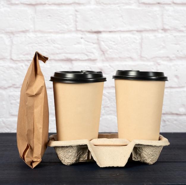 Два одноразовых стакана из коричневой бумаги с пластиковой крышкой стоят в лотке на белых контейнерах для еды на вынос