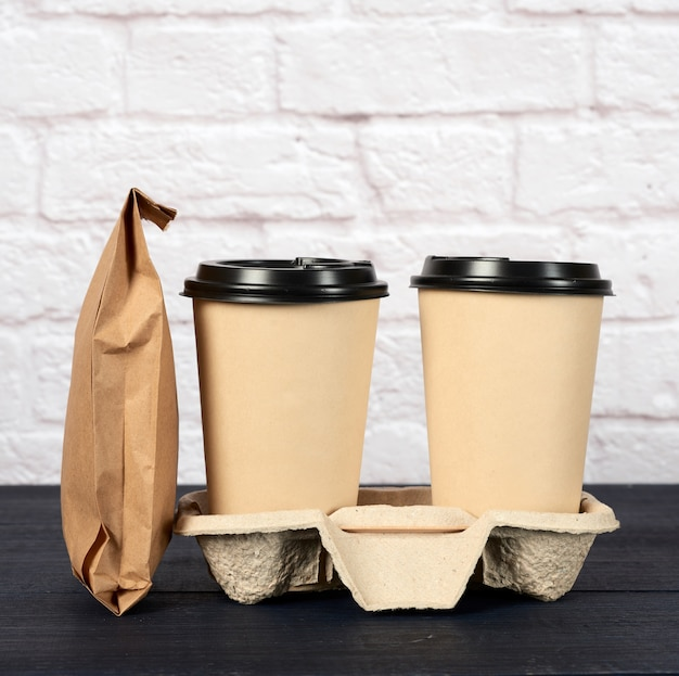 Two brown paper disposable cups with a plastic lid stand in the tray on white, takeaway containers