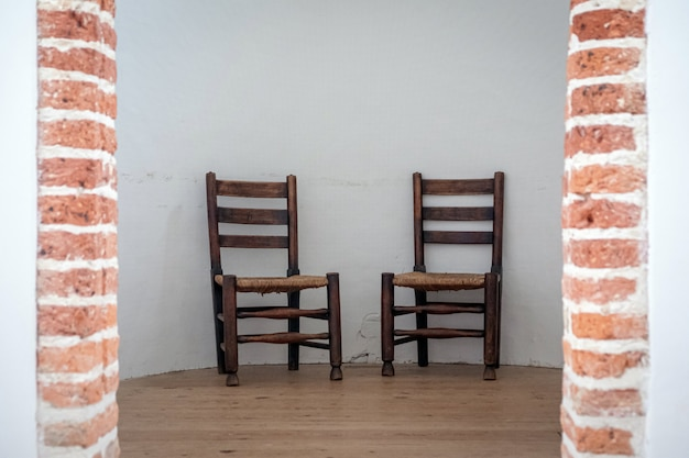 Two brown school chairs with white wall on background in natural daylight
