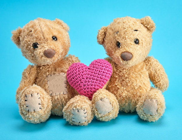 Two brown teddy bears hold a red knitted heart on a blue background