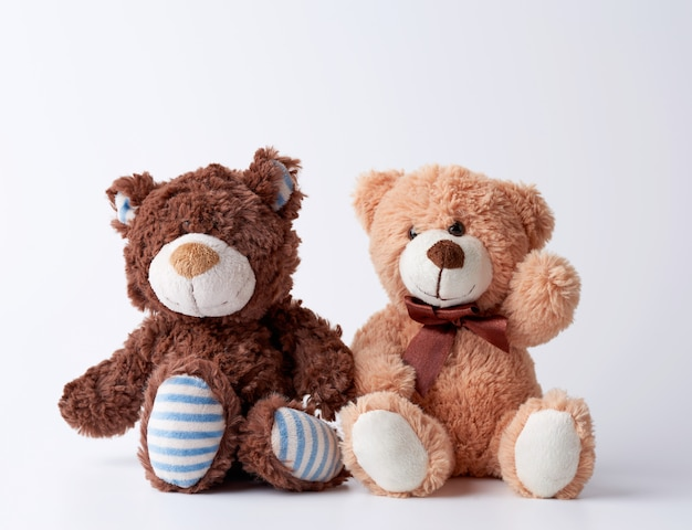Two brown teddy bears sit on a white surface