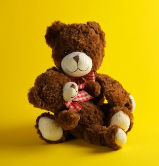 Two brown teddy bears on yellow