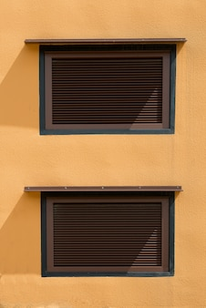 黄色の壁にシャッターが閉じている2つの茶色の窓。工業ビルの外観写真