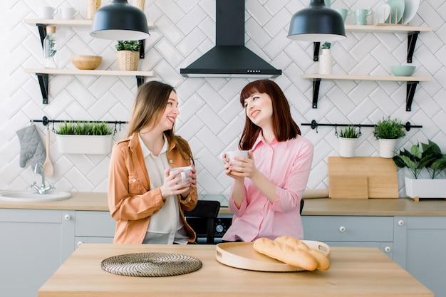 コーヒーやお茶を飲んで話している2人のブルネットの女の子の友人。キッチンインテリアの背景に一緒に朝食を食べる女性のカップル
