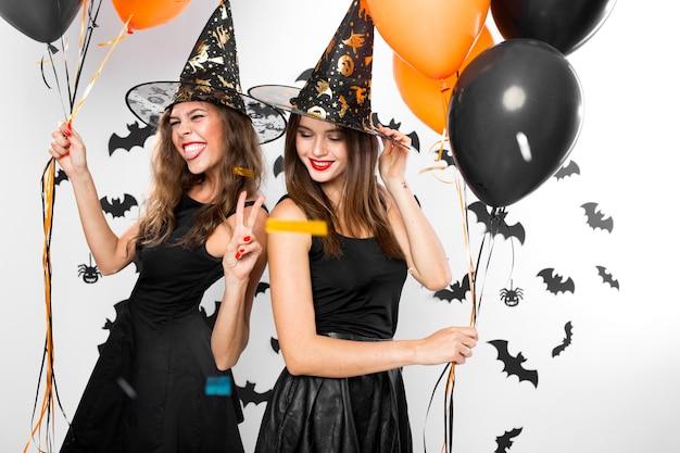 검은 드레스와 마녀 모자를 쓴 두 명의 갈색 머리 소녀는 풍선과 색종이 조각으로 즐거운 시간을 보냅니다. 할로윈 파티 .