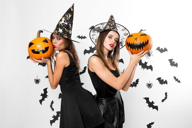 검은 드레스와 마녀 모자를 쓴 두 명의 갈색 머리 소녀가 박쥐가 있는 벽 배경에 할로윈 호박을 들고 있습니다. .