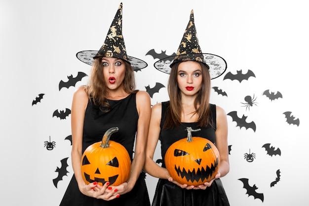 검은 드레스와 마녀 모자를 쓴 두 명의 갈색 머리 소녀가 박쥐와 함께 배경에 공포 할로윈 호박을 들고 있습니다.