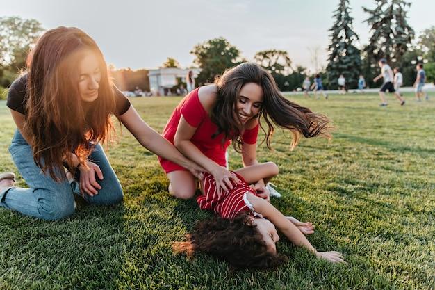 잔디밭에 앉아있는 동안 그들의 여동생과 함께 연주 두 갈색 머리 여자. 주말에 아이와 함께 시간을 보내는 숙녀의 야외 사진.