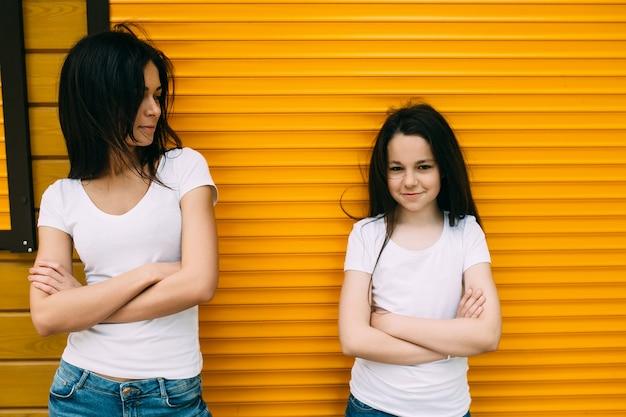 オレンジの壁に立っている2人のブルネットの女の子