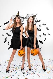 黒のドレス、魔女の帽子、ハイヒールを身に着けている2人のブルネットの女の子は、バットで背景にハロウィーンのカボチャを保持します。