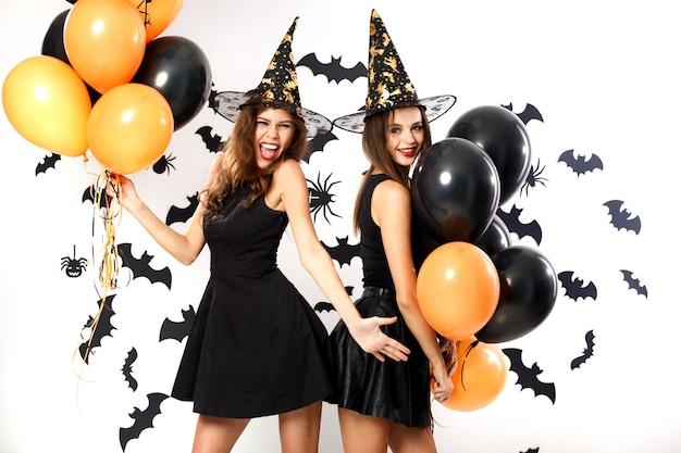검은 드레스와 마녀 모자를 쓴 두 명의 갈색 머리 여성이 박쥐가 있는 벽 배경에 검은색과 주황색 풍선을 들고 있습니다. 할로윈 파티 .