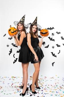 검은 드레스, 마녀 모자, 하이힐을 입은 두 명의 갈색 머리 여성이 박쥐와 함께 할로윈 호박을 들고 있습니다.