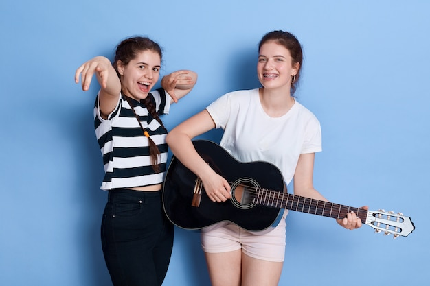 Two brunette young funny girls dance singing and playing acoustic guitar while standing isolated over blue space