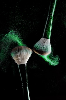 Two brushes for makeup with blue make-up shadows in motion on a black background.