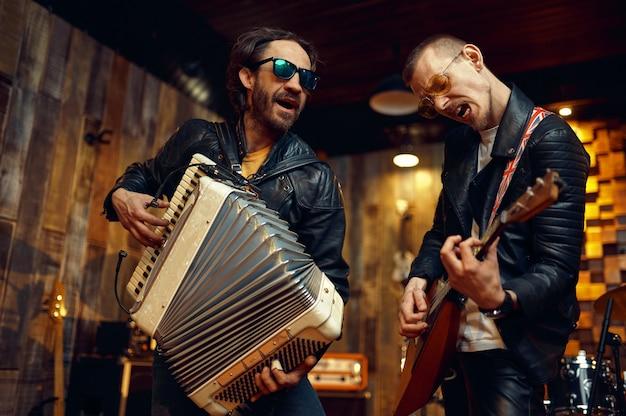 アコーディオンとバラライカを持った2人の残忍なアーティスト、ステージで演奏する音楽。ロックバンドの演奏またはガレージでの繰り返し、楽器を持った男、ライブサウンド
