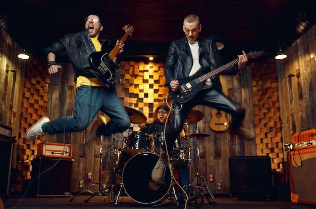 2人の残忍なミュージシャンがエレキギターでジャンプし、ステージで音楽を演奏します。ロックバンドの演奏またはガレージでの繰り返し、楽器を持った男、ライブサウンド
