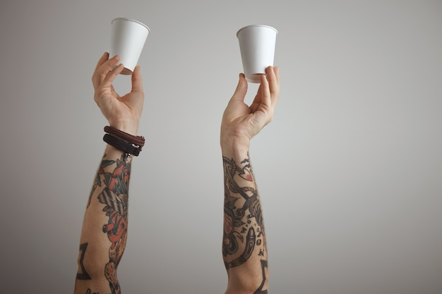 Two brutal tattooed men hands hold blank paper take away cardboard glass in the air.