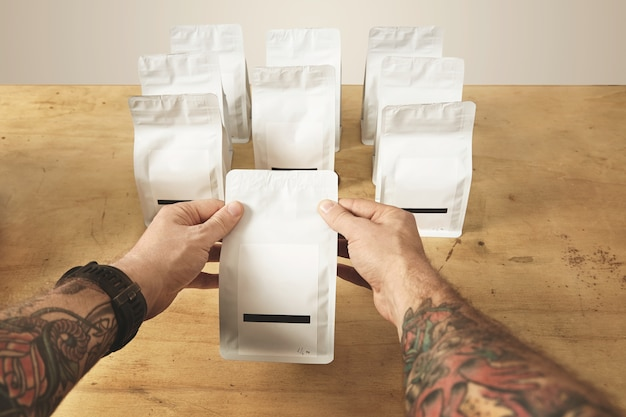 Two brutal tattooed roaster hands hold sealed package bag with tea or coffee ready for delivery and sale.