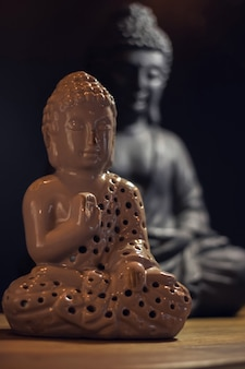 Two buddha statuettes on a wooden table