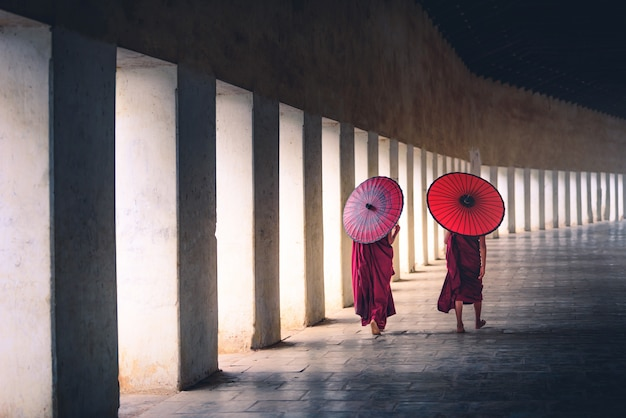 Two buddhist monk novice holding red umbrellas and walking in pagoda, myanmar.