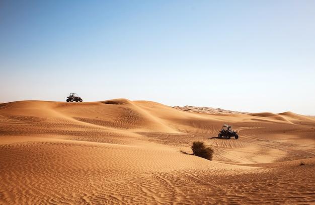 사막 풍경을 타고 있는 두 개의 버기 쿼드 바이크, 두바이 알 아위르 사파리