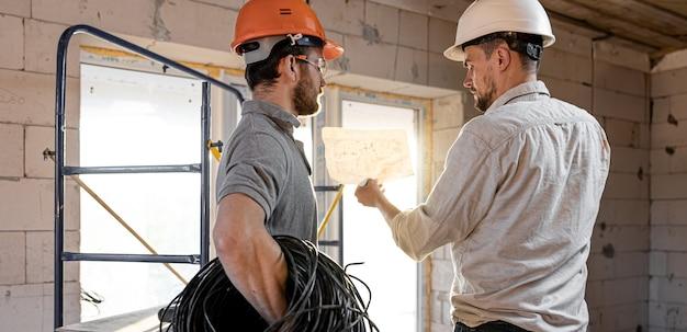 건물 사이트에서 이야기하는 두 명의 작성기 엔지니어, 작업자에게 도면을 설명하는 엔지니어.