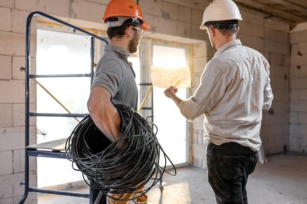 建築現場で話している2人のビルダーエンジニア、エンジニアが労働者に図面を説明する