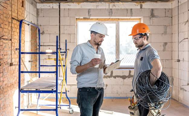 Two builder engineers talking at building site, engineer explaining a drawing to a worker.